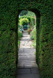 Yew arch, English garden. Pretty flagstone path through clipped yew archway towards a bench with flowers, Cotswolds, England stock images
