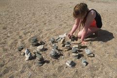 YEYSK,克拉斯诺达尔/俄罗斯:2017年5月03日:女孩建立从石头的一首歌曲在海岸 库存图片