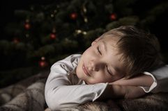 Yfhhe dreams before christmas. Sleeping and smiling boy near a new year tree with decorations Royalty Free Stock Images