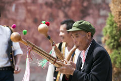 Yi Minority Group Musicians in Weishan. Yi ethnic minority men dance and play instruments in front of the central gate of the small town of Weishan in southern Royalty Free Stock Image
