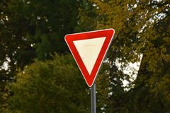 Yield or give way sign on a green background. Latvia, Europe royalty free stock images