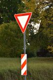 Yield or give way sign on a green background. Latvia, Europe stock photography