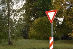 Yield or give way sign on a green background. Latvia, Europe royalty free stock photos