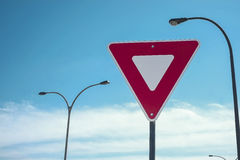 Yield road sign. On a nice blue sky wityh clouds stock photography