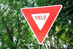 Yield Sign. Closeup red Yield Sign of tree background royalty free stock photography