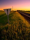Yield Sign. A yield sign stands on a rural road against a colorful sunset stock photography