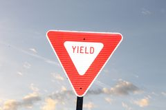 Yield sign and blue sky. Yield sign, blue sky and clouds perfect sunny day to go out royalty free stock photo