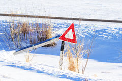 Yield sign on a broken post. Yield sign hanging from a broken post in a snow covered ditch Royalty Free Stock Photography