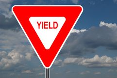 Yield Sign with clouds. In the background stock photography