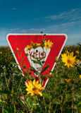 Yield Sign in Flowers. Yellow flowers almost entirely obscure yield sign along rural road - focus on yield sign stock images