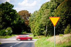 Yield sign near crossroad and rushing car Royalty Free Stock Image