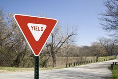 Yield Sign In A Park with clear blue sky. A yield sign on the left side of the frame with space for copy to the right and a headline across the top. A park royalty free stock photography