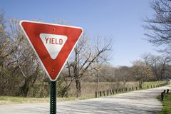 Yield Sign In a Park with dappled sunlight and a blue sky. A yield sign to the left side of the frame with copy space to the right and a headline across the top stock images