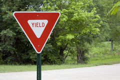 Yield Sign in a Park. A red and white `Yield` sign in a park setting with green grass, trees, and a roadway in the background stock photo