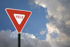 Yield Sign With Storm Clouds. A yield sign on the left side of the frame with space for copy to the right and for a headline across the top. Blue sky and storm stock photography