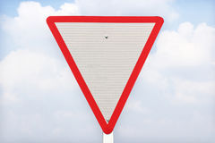 Yield traffic sign. On blue sky background stock photography