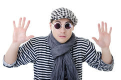 Yielding naughty and rowdy stylish young man. Yielding naughty handsome young man in stylish striped dress, glasses and cap with suitcase Stock Photography