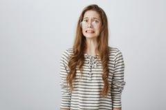 Yikes, плохая вещь случилось Портрет confused слабонервного кавказского подростка в стеклах, хмурящся, обхватывая зубы и стоковая фотография rf