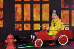 Yikes!  What a Fire!. A preschool `fireman` looking distressed in his vintage fire truck after seeing the blaze through nighttime windows Royalty Free Stock Photo