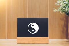 Yin e yang em um quadro-negro e em um fundo de madeira imagem de stock royalty free