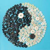 Yin und Yang-Zeichen gemacht aus Knöpfen heraus auf blauem Hintergrund Lizenzfreies Stockbild