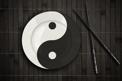 Yin yan plate over bamboo placemat with sticks Stock Image