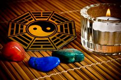 Yin yang. Oriental philosophy represented with yin yang symbol, healing stones, candle lying on bamboo Stock Images