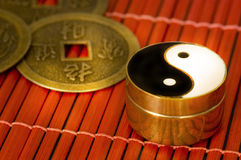 Yin-yang. Old box with three oriental coin of i-chings on red bamboo stock image