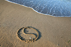 Yin Yang on the beach. The Yin Yang symbol painted in the sand of a beach Royalty Free Stock Photography