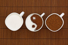 Yin Yang coffee. Three cups of sugar and coffee with the symbol of the Yin Yang on a brown background Royalty Free Stock Image