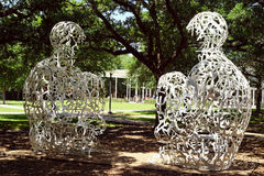 Yin and Yang of conversation. These two seated figures, made of metal letters and words, sit in silent communication on the Rice University campus in Houston Royalty Free Stock Photos