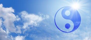 Yin Yang simbólica en bandera del cielo azul Imagen de archivo libre de regalías