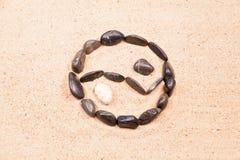 Yin yang som dras med kiselstenar på sanden Royaltyfri Fotografi