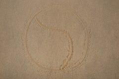 Yin yang symbol - som är skriftligt i sand på strandtextur - mjuk våg av havet royaltyfri foto