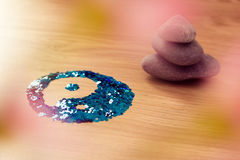 Yin yang symbol on wood with stacked zen stones Royalty Free Stock Image