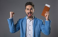 Happy smiling man holding tickets in hand. Yippee. Waist up portrait of cheerful businessman with flight documents. He is getting great news. Isolated on gray Royalty Free Stock Image