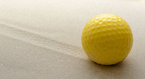 Yllow golf ball on the sand. Stock Image