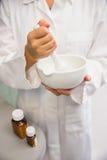 Yngre apotekare som blandar en medicin Royaltyfria Foton