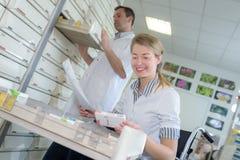 Yngre apotekare som tar medicin från hylla i apotek arkivfoto