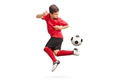 Yngre fotbollspelare som utför ett trick royaltyfria foton