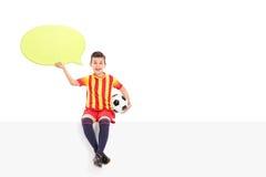 Yngre fotbollsspelare som rymmer en anförandebubbla Arkivfoton