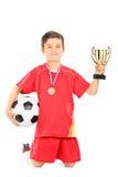Yngre fotbollsspelare som rymmer en boll och en guld- kopp Arkivfoton
