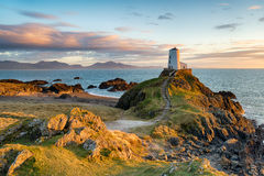 Ynys Llanddwyn in Anglesey. Sunset at Ynys Llanddwyn island on the coast of Anglesey in North Wales with the mountains of Snowdonia in the distance Royalty Free Stock Image