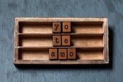 Yo te amo 我爱你在西班牙翻译 葡萄酒箱子,与老牌信件的木立方体词组 灰色石头 库存照片