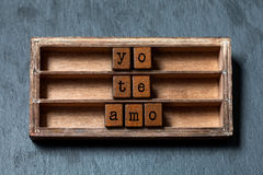 Yo te amo. I love you in Spanish translation. Vintage box, wooden cubes phrase with old style letters. Gray stone. Textured background. Close-up, up view, soft Stock Photo