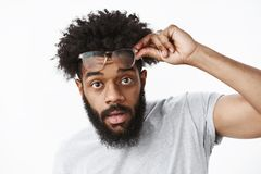 Yo what up. Portrait of good-looking cool african american bearded guy with afro hairstyle taking off glasses holding royalty free stock photos