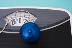 Yo-yo Diet. Blue yo-yo sitting on scales on blue background Royalty Free Stock Photos