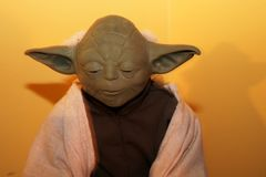 Yoda doll from Star Wars movie alien creature. Yoda doll from Star Wars movie. He has big ears and a robe wrapped around him. He is looking down. His alien skin Royalty Free Stock Photo