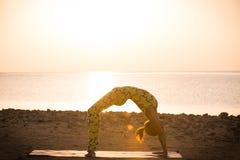Yogaövning. Kvinnan som gör bron, poserar Royaltyfri Foto