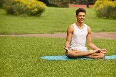 Yogaövning Stående av den idrotts- mannen som gör en yoga på sommar p fotografering för bildbyråer
